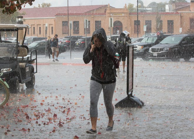 Natalie Swanson, runs to Corbett Center  as hail falls over New Mexico State University, Wednesday October 31, 2018.