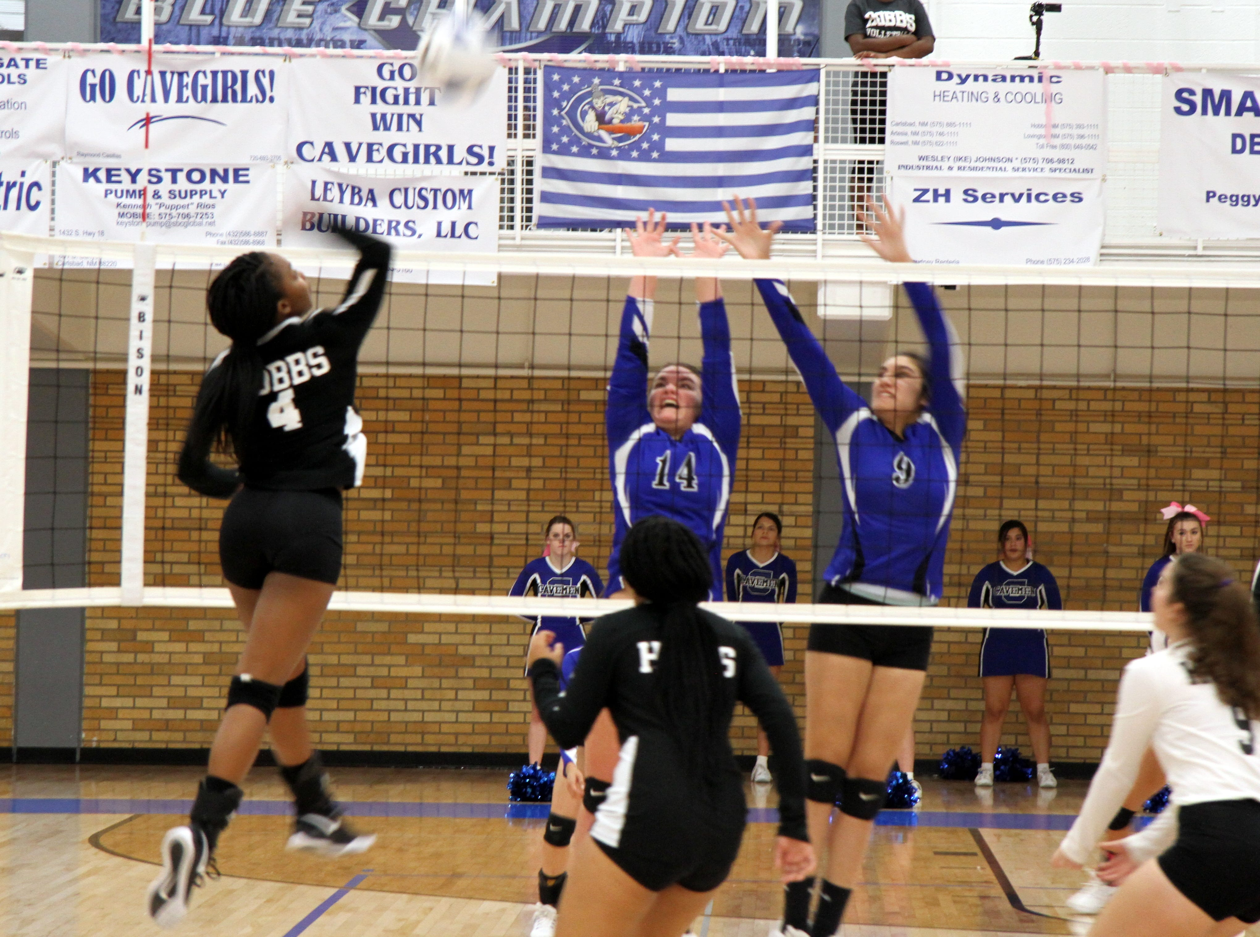 Danaye Boss (14) and Serena Rodriquez (9) go for a block during Tuesday's match against Hobbs.