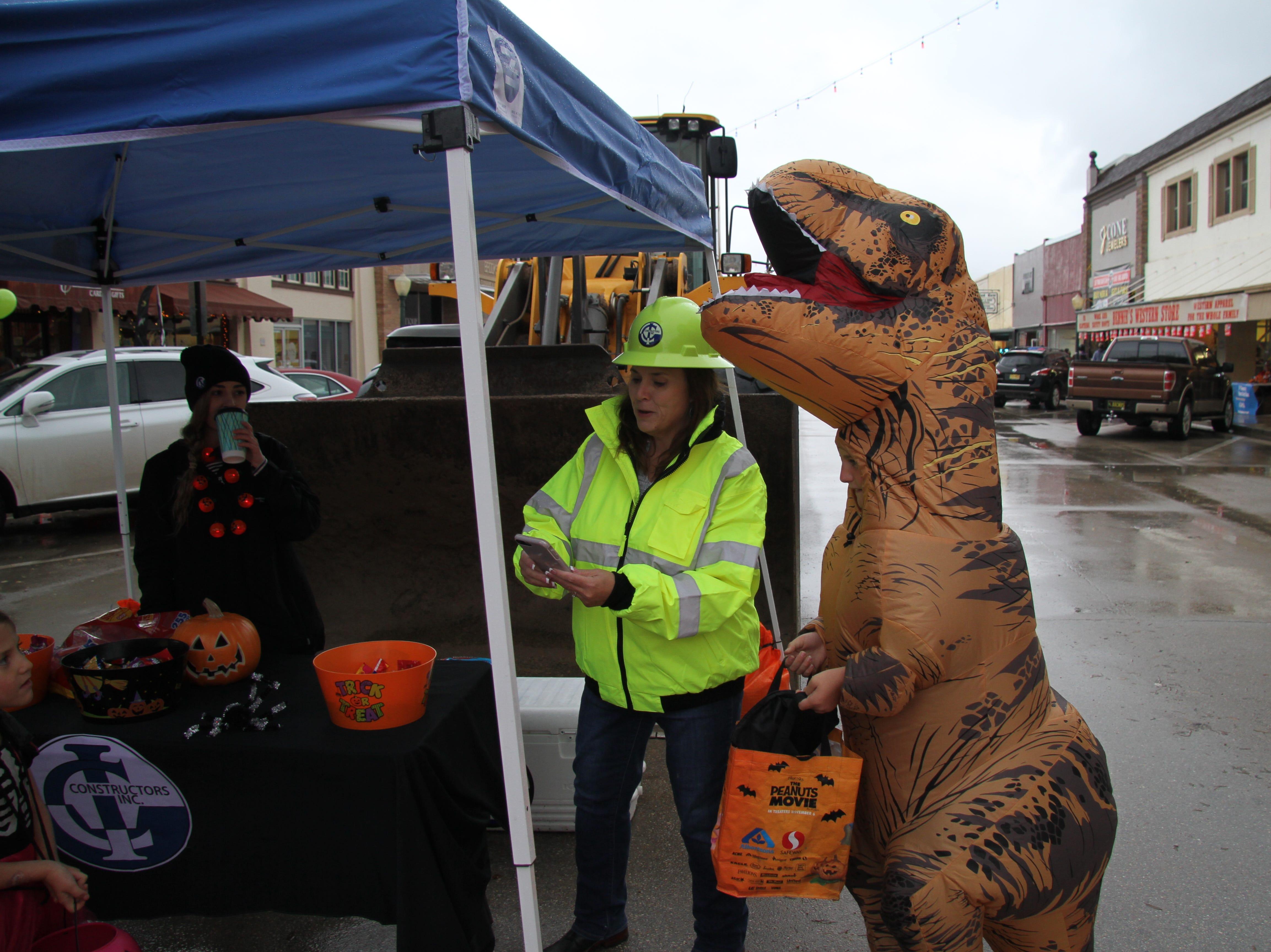 T-Rex gets a treat during Halloween's MainStreet Fall Fest.