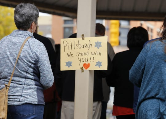 A sign is displayed Tuesday during a vigil at Orchard Park in Farmington honoring the victim's of Saturday's synagogue shooting in Pittsburgh.