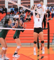Canton's Amanda Wilyard (9) makes the set against Novi front row players Caleigh Robinson (left) and Gaby Cummings (middle).