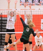Novi's Rachel Karr (10) goes on the attack against the Canton front row block which includes Tori Balog (11).