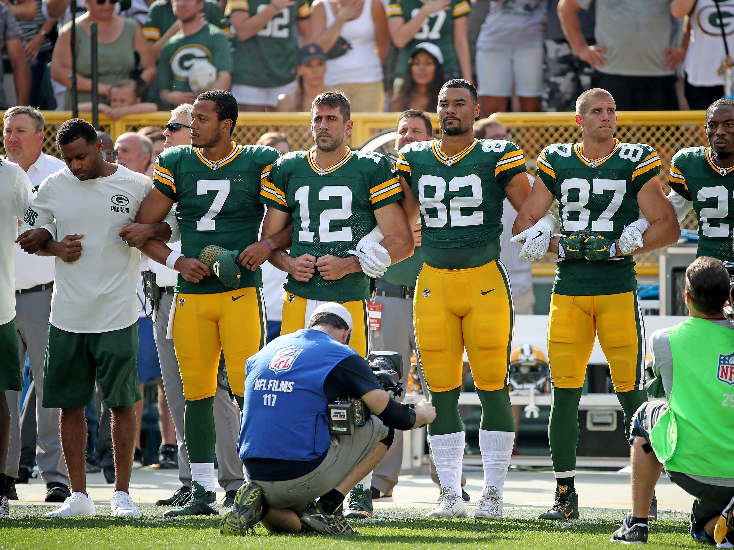 Green Bay Packers quarterback Aaron Rodgers (12), quarterback Brett Hundley (7), tight end Richard Rodgers (82), wide receiver Jordy Nelson (87) and free safety Ha Ha Clinton-Dix (21) link arms in solidarity during the National Anthem before the game against the Cincinnati Bengals Sunday, September 24, 2017 at Lambeau Field in Green Bay, Wis.