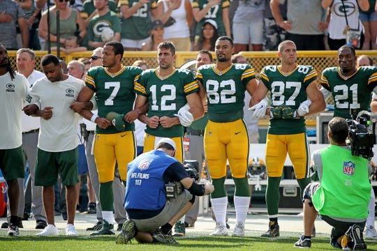 Packers quarterback Aaron Rodgers (12) joins quarterback Brett Hundley (7), tight end Richard Rodgers (82), wide receiver Jordy Nelson (87) and free safety Ha Ha Clinton-Dix (21) in linking arms in solidarity during the national anthem before a game against Cincinnati on Sept. 24, 2017.