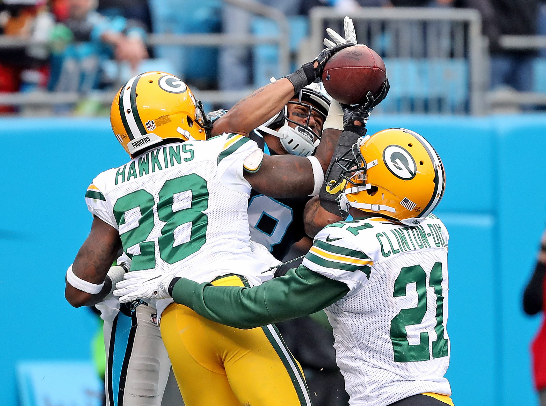 Green Bay Packers cornerback Josh Hawkins (28) and free safety Ha Ha Clinton-Dix (21) try to break up a pass  to wide receiver Damiere Byrd (18) against the Carolina Panthers Sunday, December 17, 2017 at Bank of America Stadium in Charlotte, NC. Initially ruled incomplete, the pass was ruled a touchdown on review.