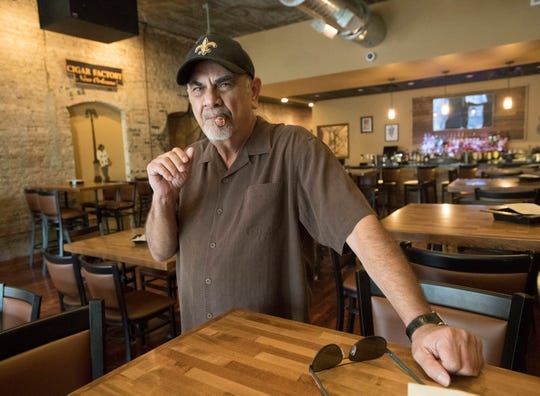 Dave Sharruf, the owner of the Cigar Factory in downtown Pensacola, enjoys a cigar in October 2018. Sharruf has plans to open a new bar and restaurant in the location of the former Hopjacks in downtown Pensacola.