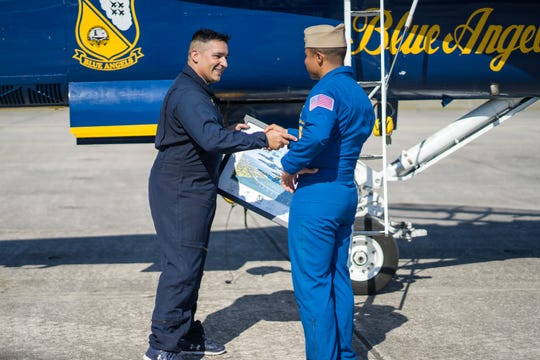Sgt. Rich Aloy shakes hands with Lt. Cmdr. Andre Webb after he receives a framed photo commemorating Aloy's flight on Wednesday, Oct. 31, 2018.