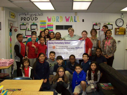 Students and faculty at Ensley Elementary School celebrate their donation of $1,041 to the Pensacola Humane Society.