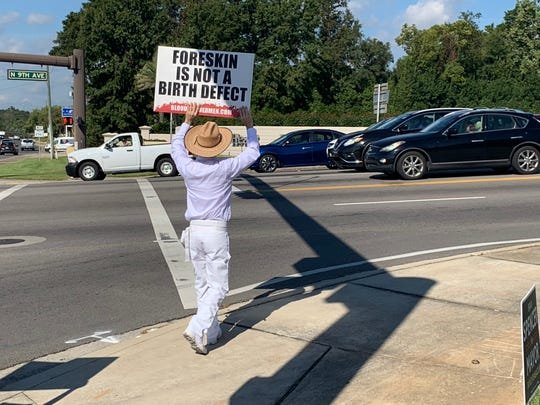 A protester holds a sign for people driving by at the corner of Bayou Boulevard and North Ninth Avenue in Pensacola on Wednesday, Oct. 31.