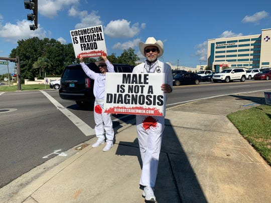 Harry Guiremand, right, holds a sign during a Bloodstained Men and their Friends protest at the corner of North Ninth Avenue and Bayou Boulevard in Pensacola. The group was in town protesting male circumcision.