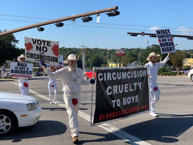 A group of protesters from Bloodstained Men and Their Friends walks across North Ninth Avenue on Wednesday, Oct. 31 as part of a demonstration against male circumcision.