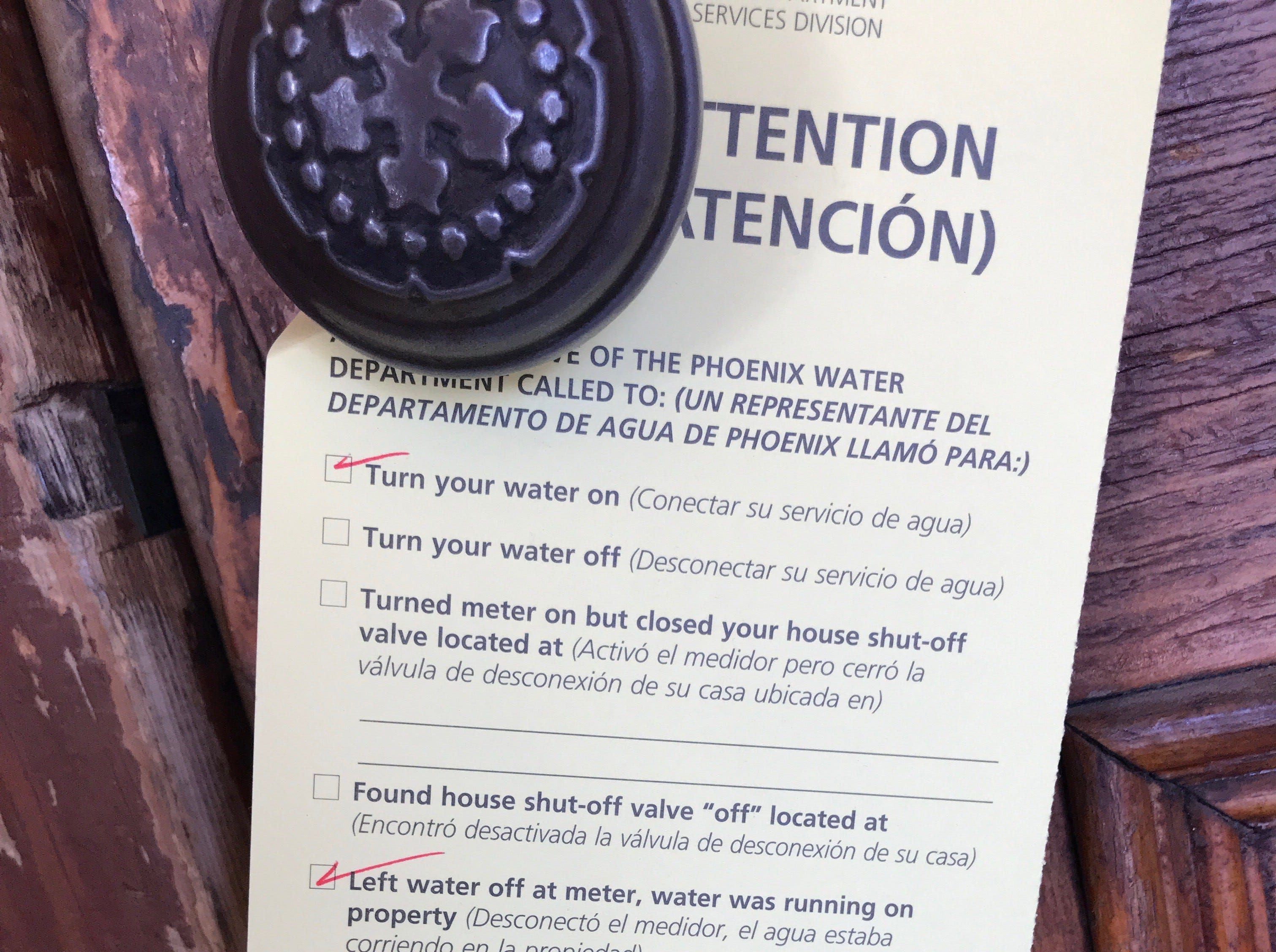 "Phoenix Water Department's sign hangs on the door of The Rose & Crown Pub at 628 E. Adams St., Phoenix, on Oct. 31, 2018. The box indicating officials called to ""turn your water on"" is checked."