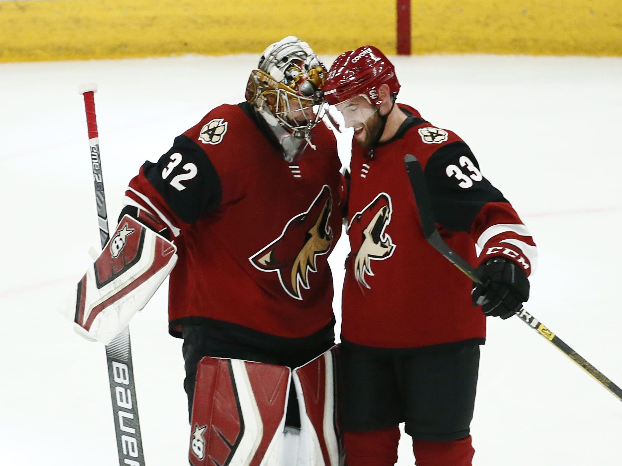 Arizona Coyotes goalie Antti Raanta and Alex Goligoski (33) celebrate their 5-1 win over the Ottawa Senators on Oct. 30, 2018 at Gila River Arena.