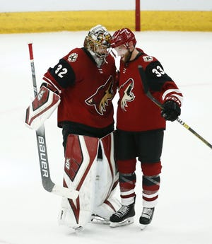 Goaltender Antti Raanta and defenseman Alex Goligoski celebrate after a 5-1 victory over the Senators on Tuesday at Talking Stick Resort Arena.