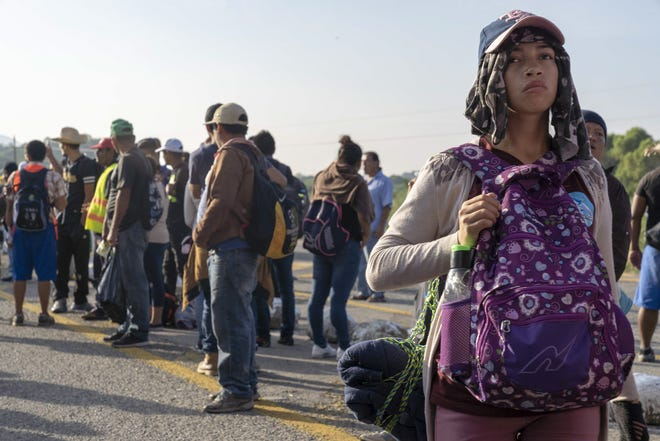 The caravan migrants are hitching rides on trucks and in pickup trucks and cars at an immigration checkpoint as immigration officers watch.