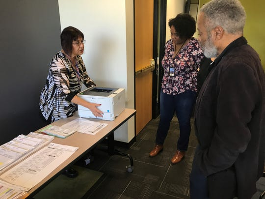 Anita Aguilar, a board worker trainer, explains how to fix a printer jam at the training for Maricopa County poll workers.