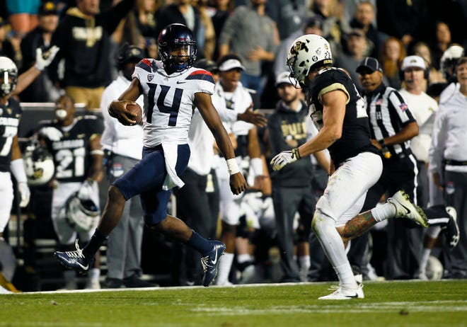 Arizona Wildcats quarterback Khalil Tate (14) runs for a long gain as Colorado Buffaloes defensive back Ryan Moeller (25) defends at Folsom Field.