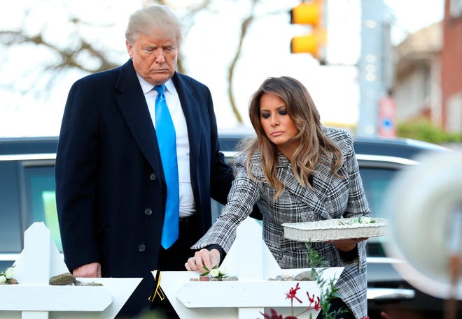 President Donald Trump and first lady Melania Trump put down stones from the White House and flowers at a memorial outside for those killed at the Pittsburgh's Tree of Life Synagogue in Pittsburgh, on Oct. 30, 2018.