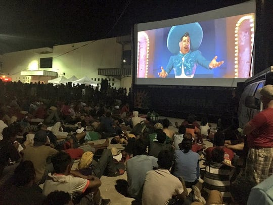 "Migrants from Central American caravan watch the Disney movie ""Coco"" movie on Oct. 30 while others patiently wait in line to be served food coordinated by the municipal government of Juchitán de Zaragoza in Oaxaca, southern Mexico."