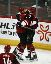 Alex Galchenyuk receives a hug from Jason Demers after scoring a goal against the Senators during the first period of a game Oct. 30 at Gila River Arena.