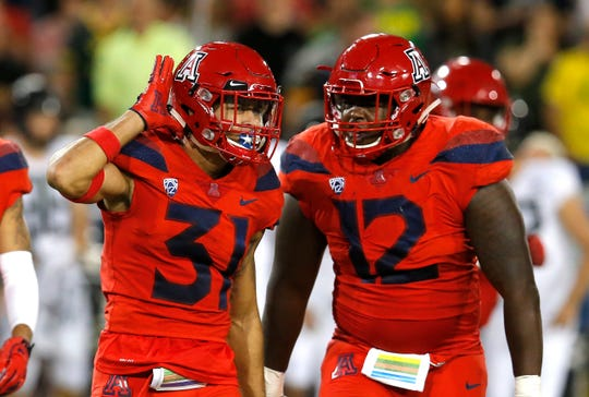 Arizona safety Tristan Cooper (31) celebrates with JB Brown after defeating Oregon 44-15 during an NCAA college football game, Saturday, Oct. 27, 2018, in Tucson, Ariz. Arizona defeated Oregon 44-15.