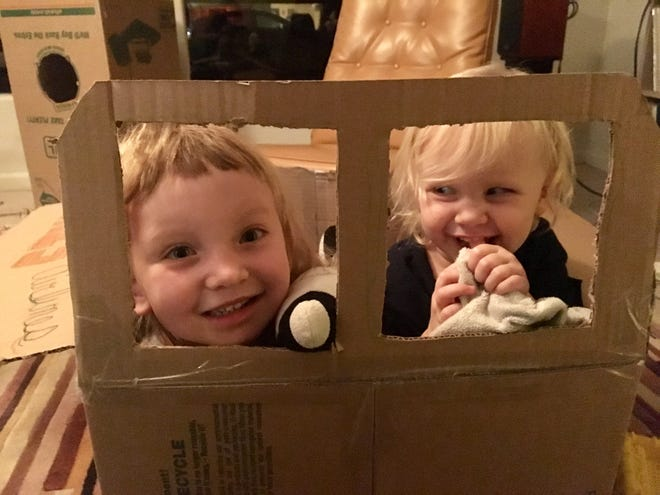A cardboard box airplane can hold two, plus a couple stuffed animals and blankeys.