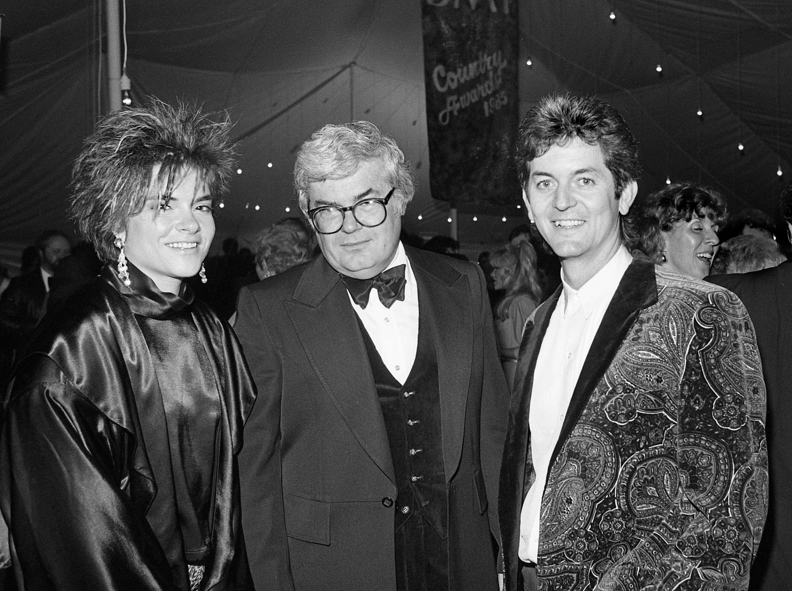 Rosanne Cash and husband Rodney Crowell flank an unidentified guest at the BMI Awards banquet on Oct. 15, 1985, in Nashville, Tennessee.