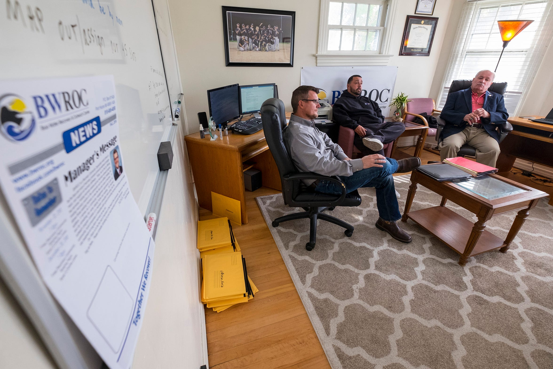 The front page of the BWROC's upcoming newsletter sits on a shelf while center Manager Patrick Patterson, left, meets with volunteers Justin Kroll, center, and Nino Cimini on Tuesday, Oct. 30, 2018, in the center's office in The Roost in Port Huron.