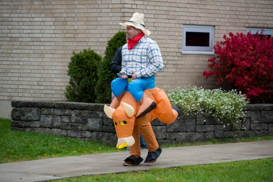 STEAM Academy at Woodrow Wilson principal Joseph Kramer exits the school dressed as a cowboy riding a bull Wednesday, Oct. 31, 2018 during the school's Halloween parade.