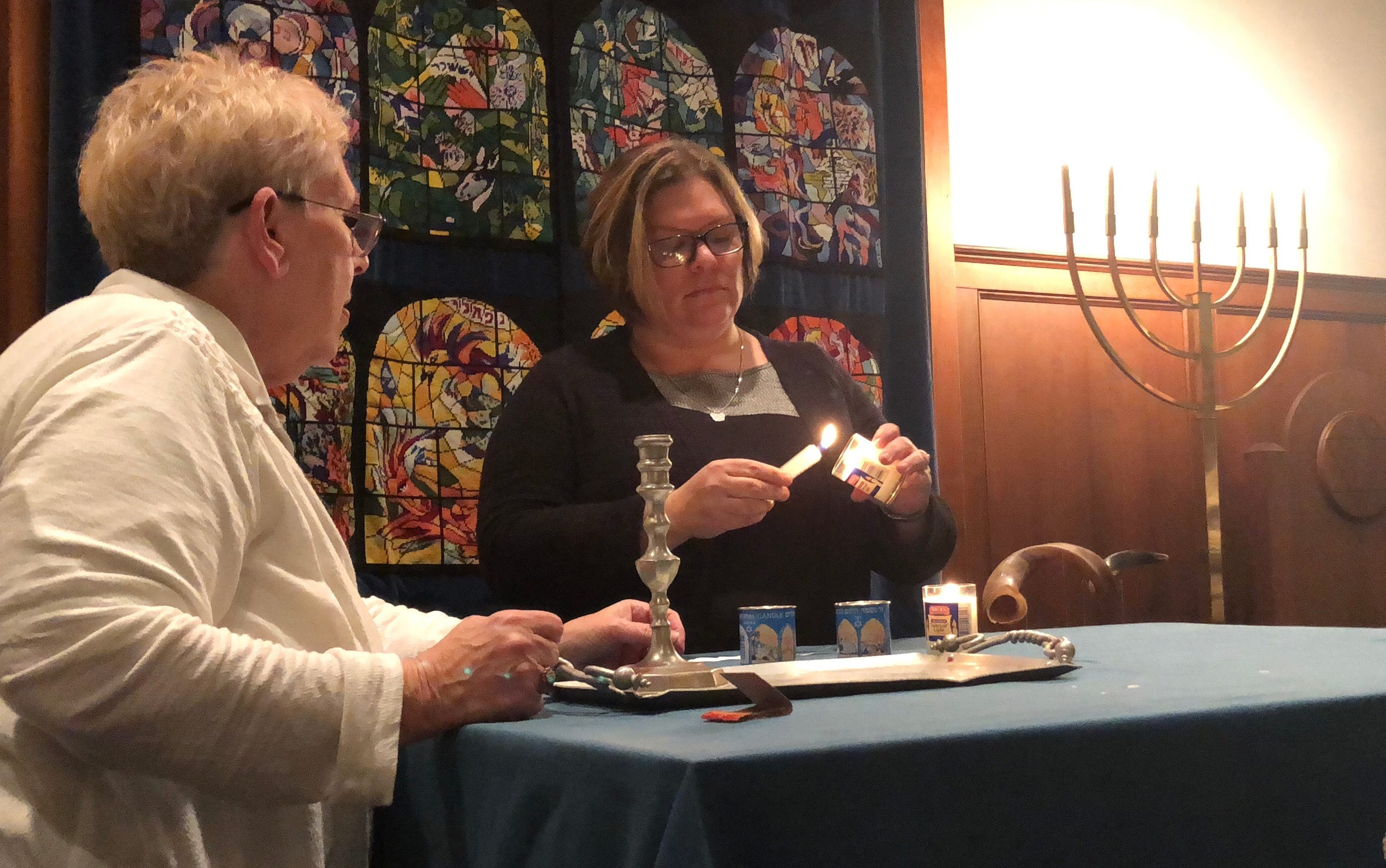 Jessica Doubell (right), Chambersburg, lights a candle in memory of a victim during a memorial service at Congregation Sons of Israel in Chambersburg the evening of Tuesday, Oct. 30. The event was held to honor 11 Jewish people who were killed in a shooting in Pittsburgh a few days earlier. Also pictured: Lynne Newman (left), a member of the congregation.