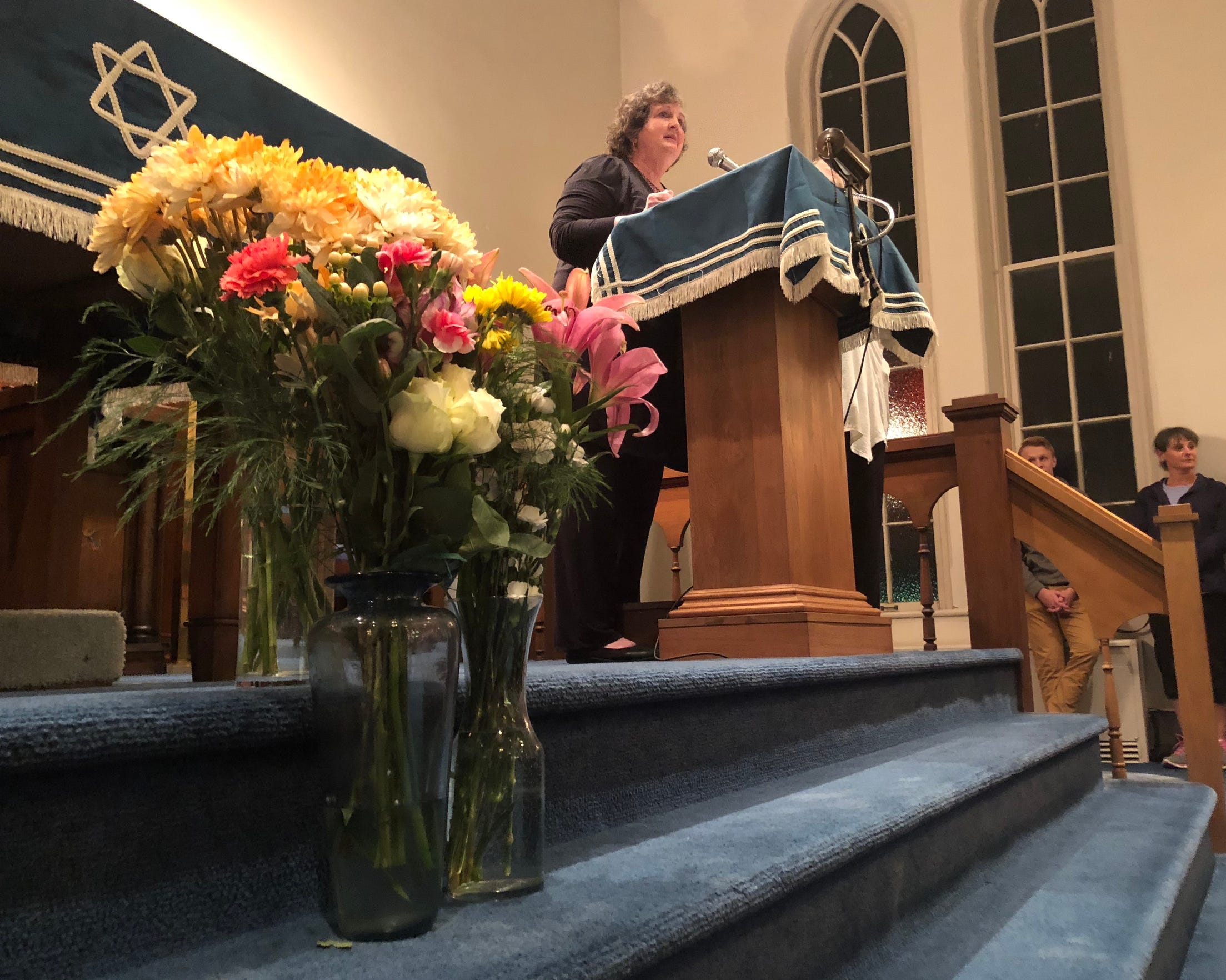Flowers can be seen in the front of the room at Congregation Sons of Israel in Chambersburg during a memorial service the evening of Tuesday, Oct. 30. The event was held to honor 11 Jewish people who were killed in a shooting in Pittsburgh a few days earlier, and the flowers were left on the steps of the building by an anonymous person the day of the attack. Also pictured: Borough councilmember Sharon Bigler.