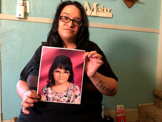 """In this Sept. 21, 2018, photo, Lee Ann Berkebile holds a photo of herself as a child, taken in her home in Johnstown, Pa. Berkebile says she was molested by her pediatrician in 1994. Pennsylvania regulators are being harshly criticized for clearing Dr. Johnnie """"Jack"""" Barto, a pediatrician who'd been accused of sexual abuse 20 years ago and who's now charged with molesting many more children since. (AP Photo/Michael Rubinkam)"""