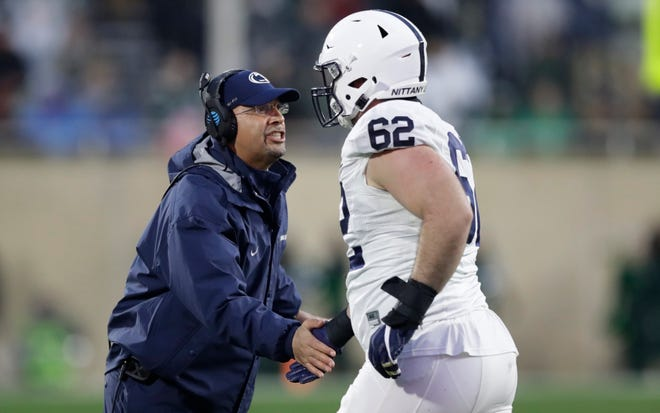 Penn State head coach James Franklin greets Penn State offensive lineman Michal Menet (62) during the second half of an NCAA college football game, Saturday, Nov. 4, 2017, in East Lansing, Mich. (AP Photo/Carlos Osorio)