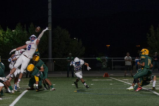 Reno's Wyatt Draeger (9) blocks an extra point attempt by Manogue's Gonzalo Martinez in their football game September 21 at Bishop Manogue.