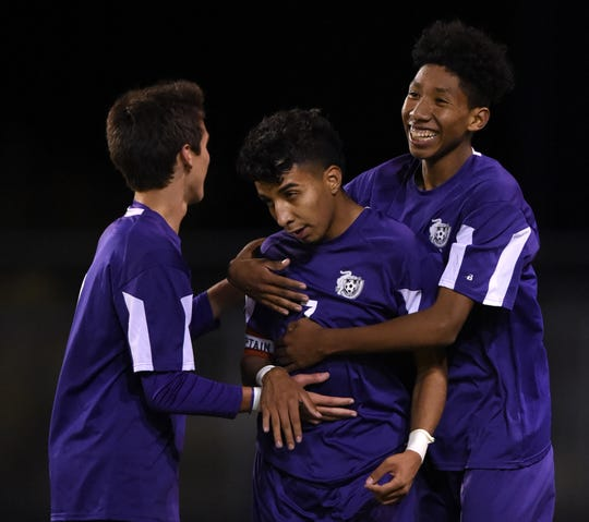 Spanish Springs players Lucca Casci, left, and Jose Valdivia, right, celebrate a goal by Wilmer Hernandez, center, to make it a 3-0 score in the second period on Monday at Spanaish Springs.