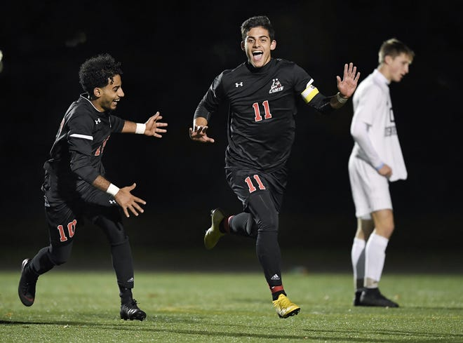 Hilton's Noah Malta, center, celebrates his second goal, the game winner, with Hussian Ali during the Section V Class AA championship game at Spencerport High School on Tuesday, Oct. 30, 2018. Hilton claimed the Class AA title with a 2-1 win over Rush-Henrietta.