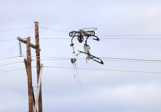 In this Oct. 30, 2018 photo, landing gear from a helicopter dangles from power lines, after a deadly helicopter crashed in Beekmantown, N.Y. The National Transportation Safety Board says investigators are headed to the site a day after the helicopter hit power lines and burst into flames over a plowed farm field along a rural road in northern New York.