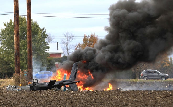 In this Oct. 30, 2018 photo, flames and smoke rise from pieces of a deadly helicopter crash in Beekmantown, N.Y. The National Transportation Safety Board says investigators are headed to the site a day after the helicopter hit power lines and burst into flames over a plowed farm field along a rural road in northern New York.