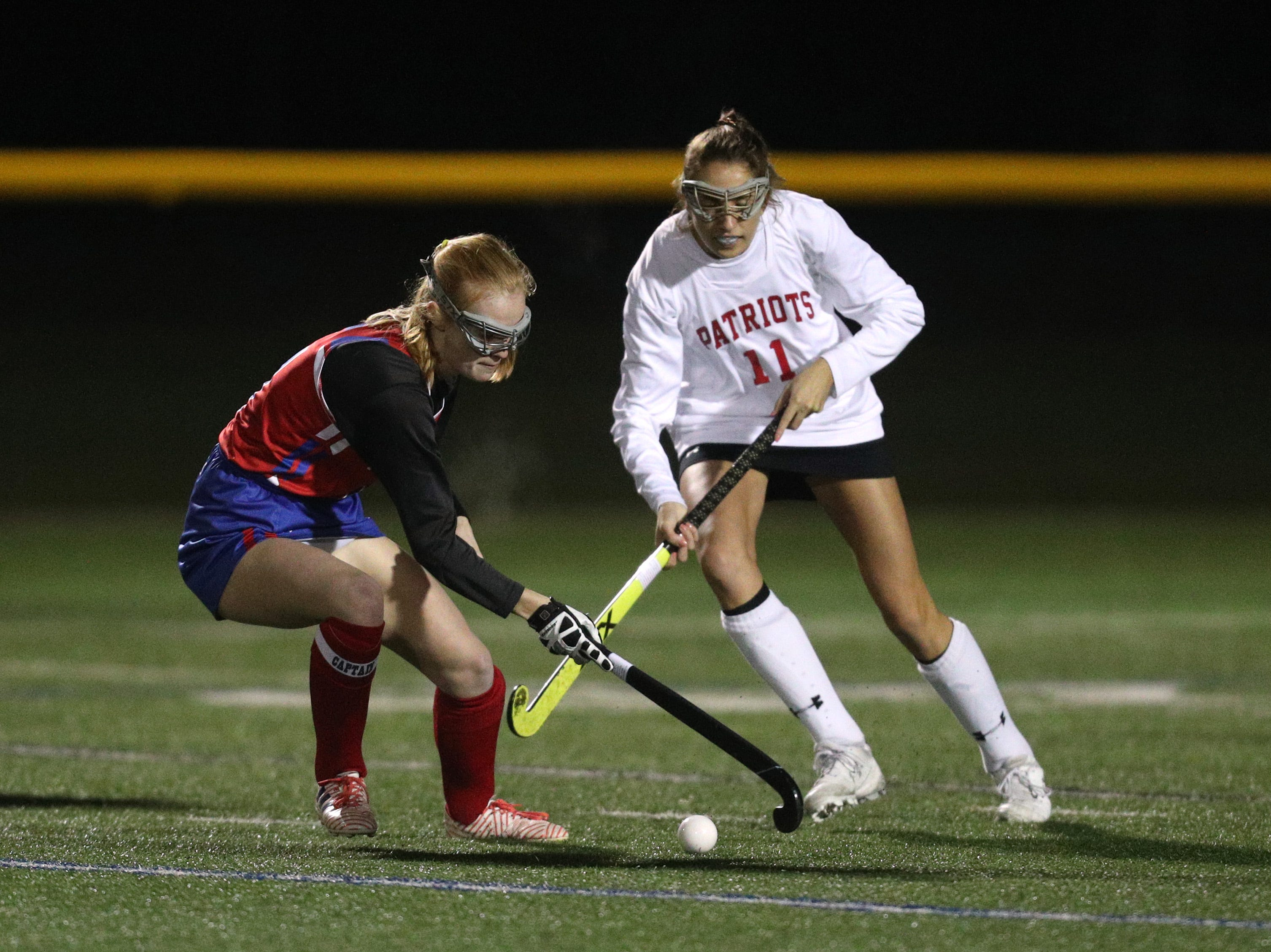 Fairport's  Maggie Phipps carries the ball out of pressure by  Penfield's Kate Mosca.