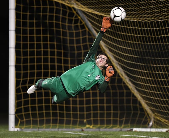 Rush-Henrietta goalie Ethan Scheuer makes a diving save during the Section V Class AA championship.
