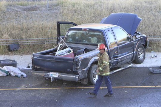 A firefighter looks at the scene of a wreck on Interstate 5. A Ford pickup going on the Hilltop Drive overcross plunged onto the freeway Thursday morning, Oct. 31, 2013, snarling traffic.