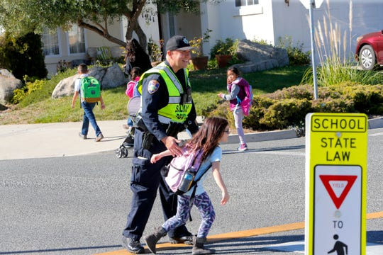 New Republic Elementary School student Brienna Vail, 7, finishes crossing the street Tuesday after hugging Richard Lopez, a Salinas Police school resource officer with the Santa Rita Union Elementary School District.