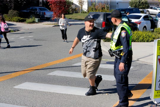 Chuck Vail, on his way to pick up his daughters, greets Salinas police school resource officer Richard Lopez Tuesday at New Republic Elementary School.