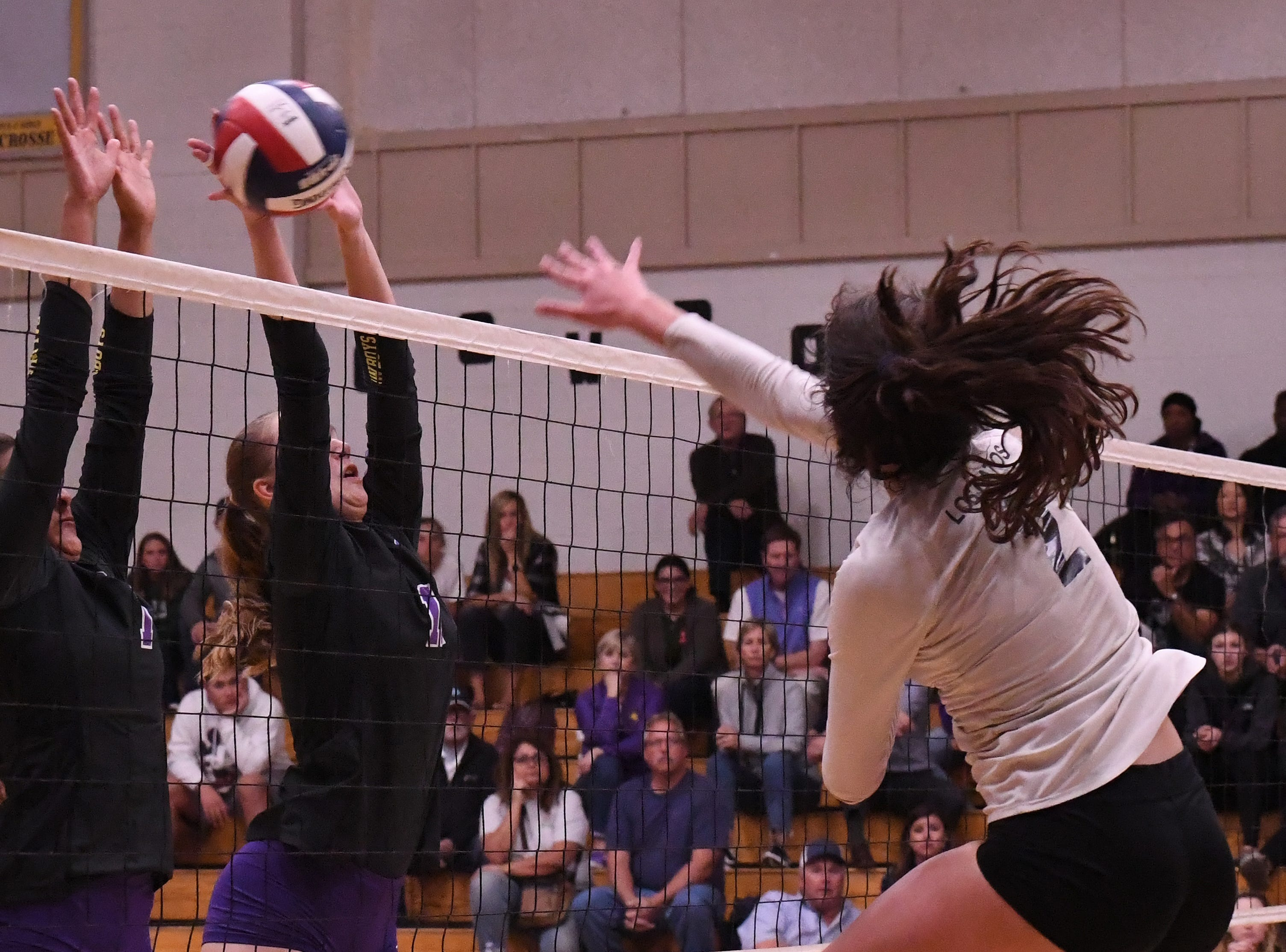 Senior setter Aloha Delk (1) and middle blocker Savannah Maker (11) reach for a spiked ball.