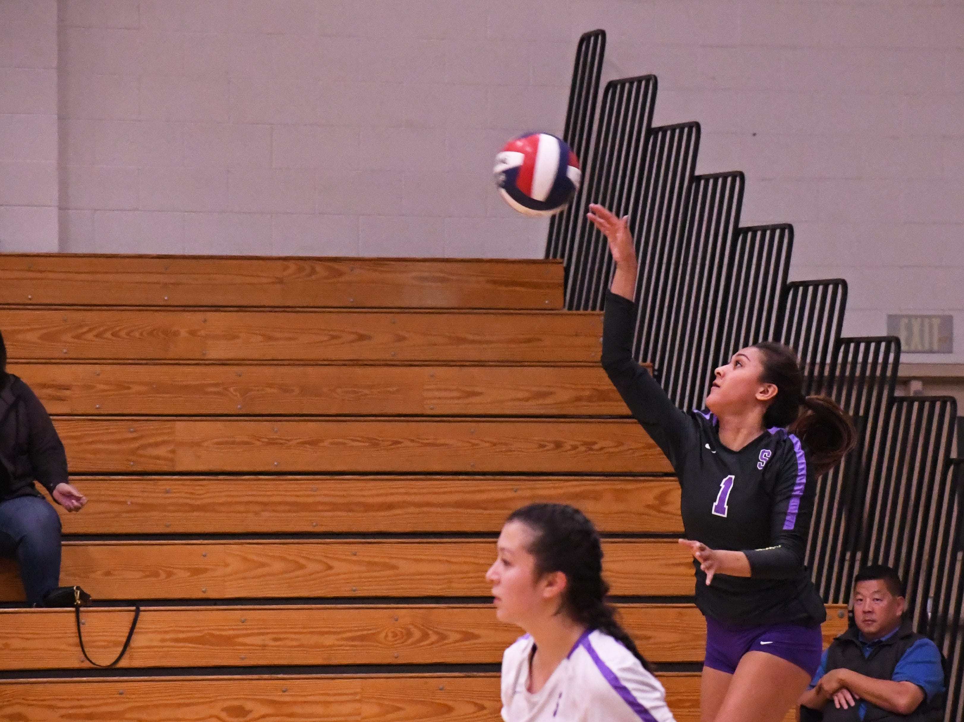 Right side hitter Aloha Delk (1) hits a serve in the first set.