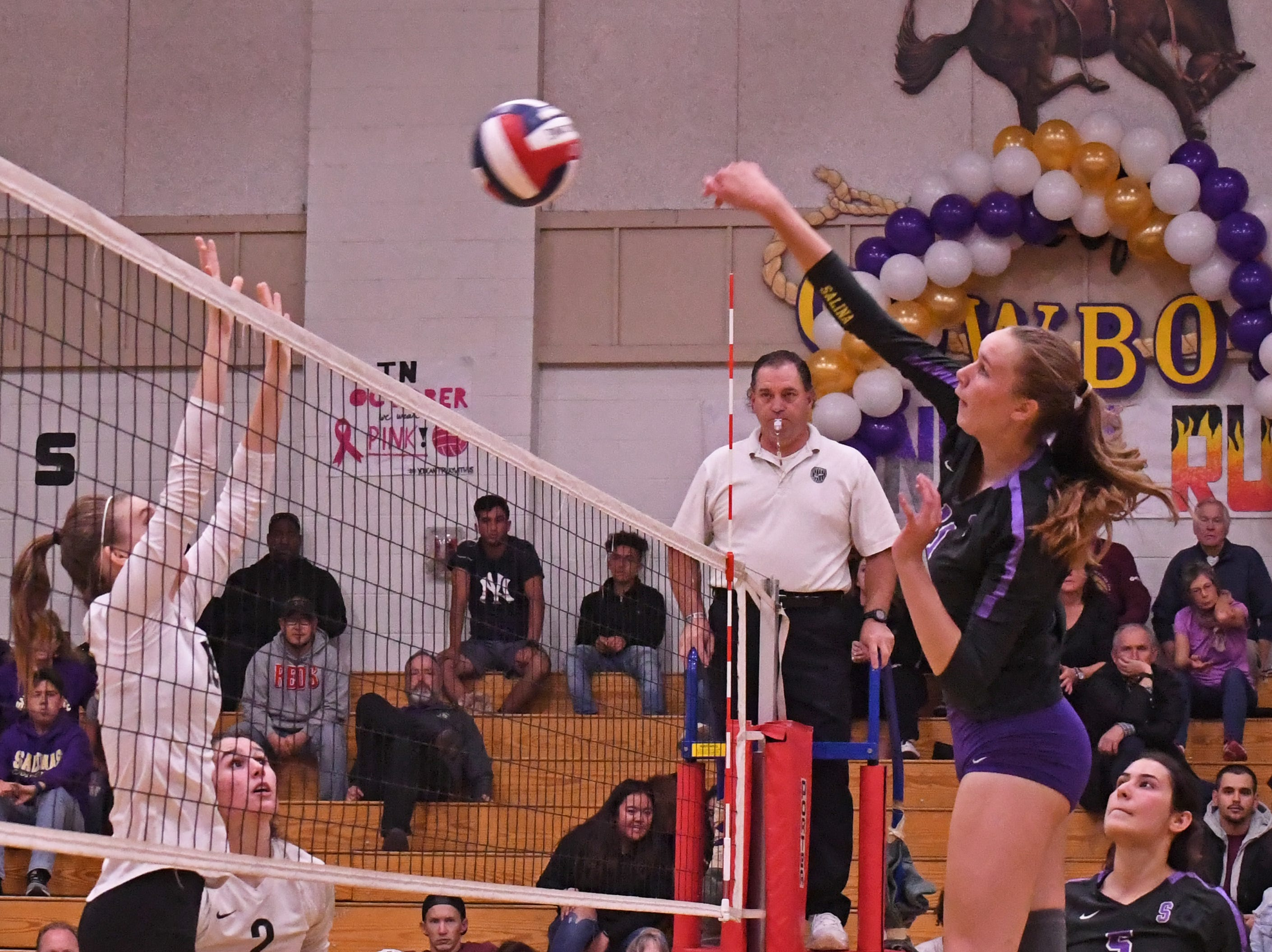 Middle blocker Savannah Maker (11) spikes the ball to Los Gatos' side in the first set.