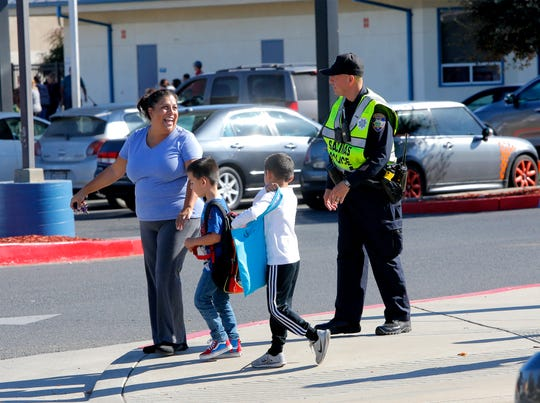A woman and two children chat Tuesday with Salinas police school resource officer Richard Lopez, who serves the Santa Rita Union School District.
