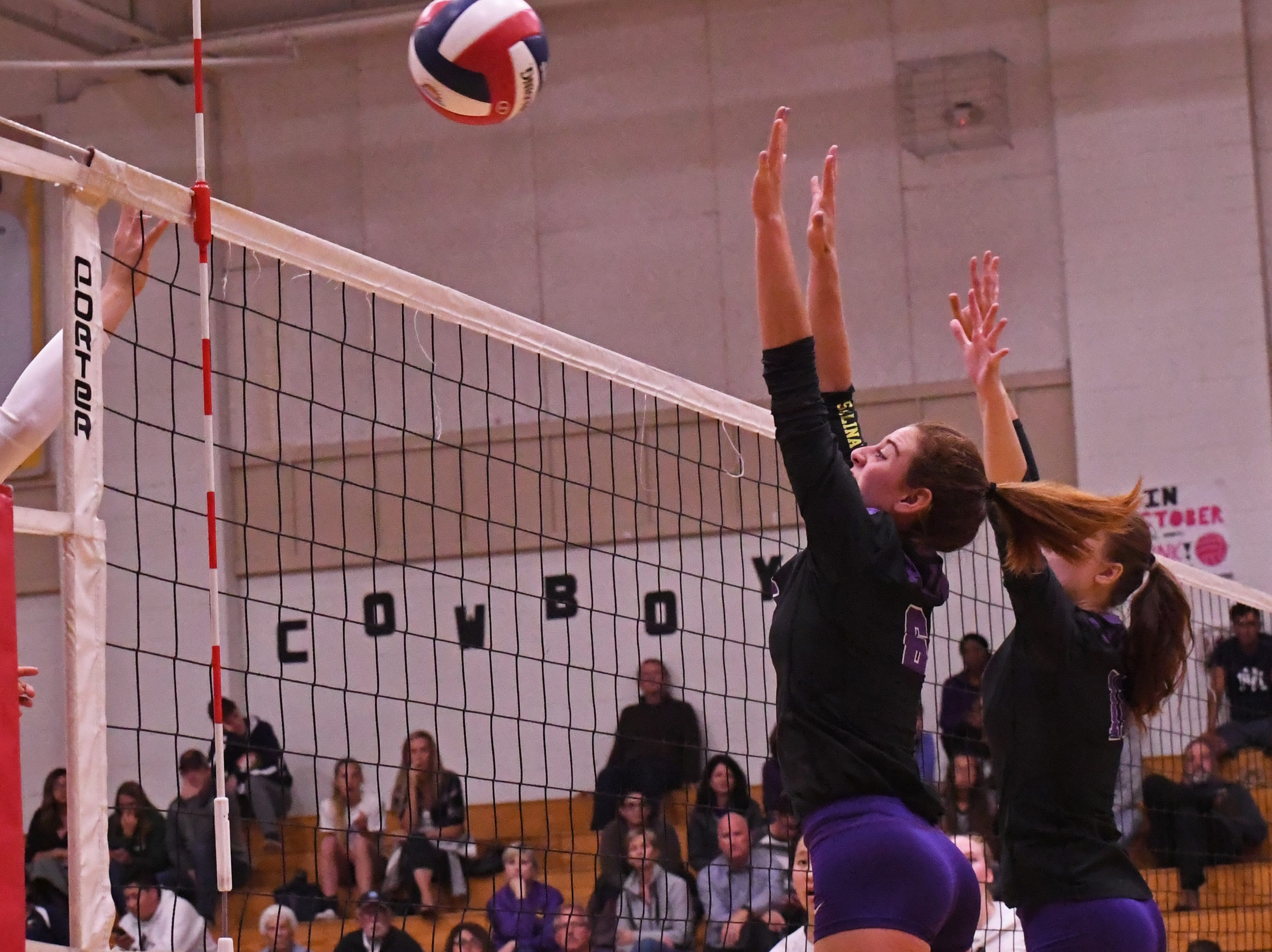 Outside hitter Kylee Moore (6) and middle blocker Savannah Maker (11) reach for the ball in the third set.