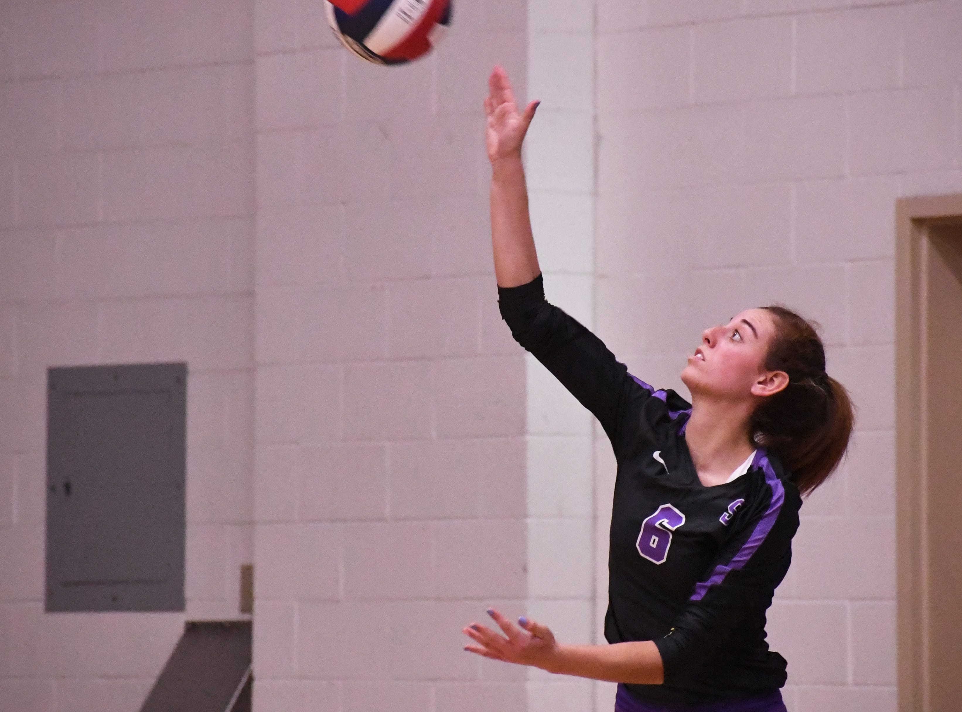 Outside hitter Kylee Moore (6) hits a serve in the third set.
