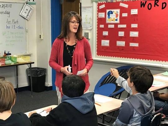 Sixth grade math teacher  Rhonda Poncelet passes out index cards to students during class Oct. 24 at Whittier Middle School.